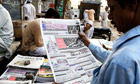 Man reading Pakistani newspaper