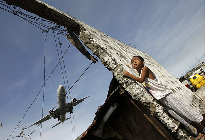 24 hours in pictures: Manila, Philippines: A boy looks at a passenger plane as it lands=