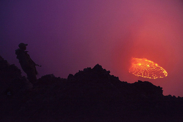Congolese soldier at the Virunga national park looks into a boiling lava lake in the crater of the Nyiragongo volcano