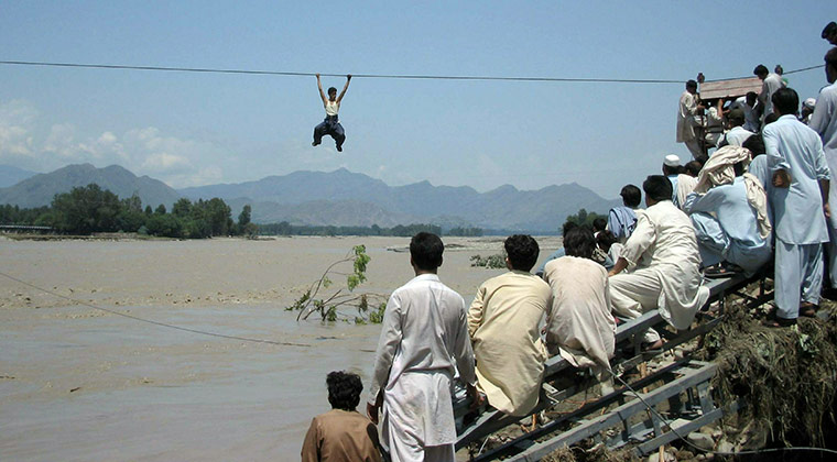 24 hours in pictures:  Pakistani flood survivor climbs a rope to cross the river in Chakdara