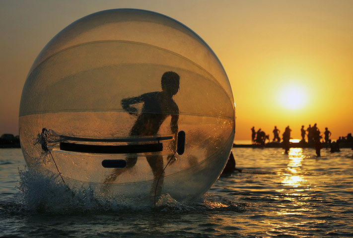 A schoolboy playing inside a giant inflatable plastic sphere ...