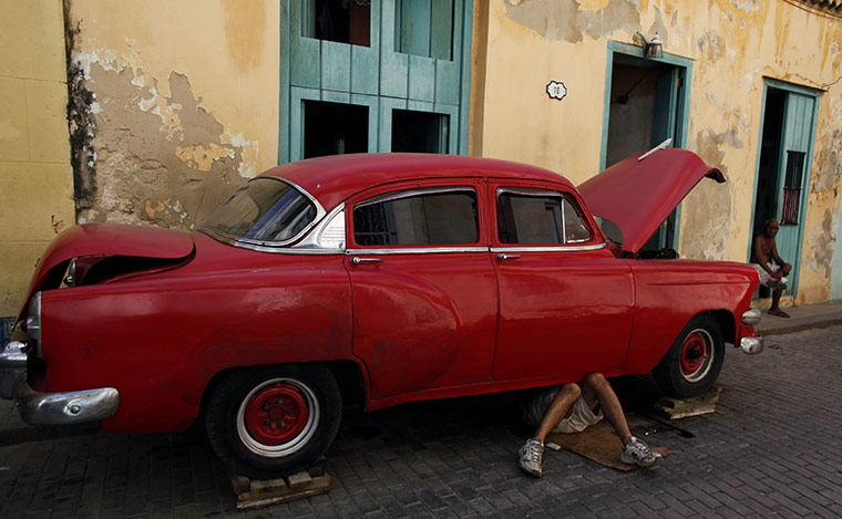 24 hours in pictures: Havana, Cuba: A man repairs an old car