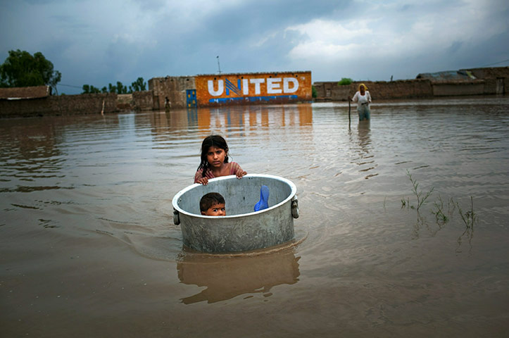 Pakistan update: A girl floats her brother across flood waters whilst salvaging valuables