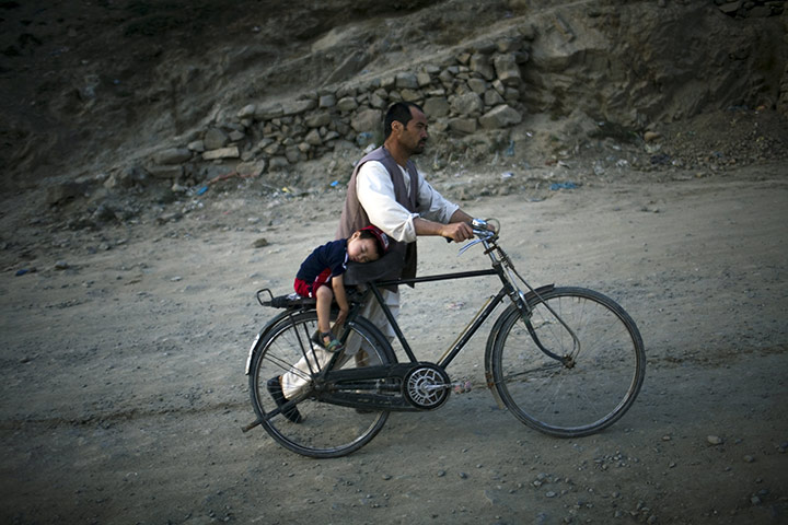 24 hours in pictures: Kabul, Afghanistan: A father pushes his sleeping son on a bicycle