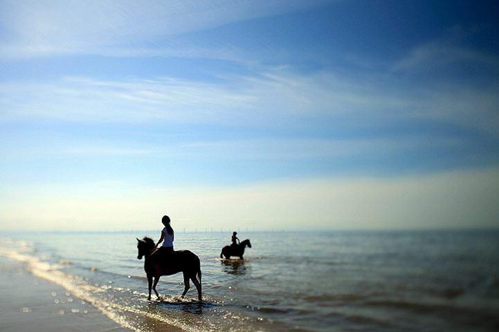 Girls ride their ponies through the sea as they make the most of the good weather at Formby Point