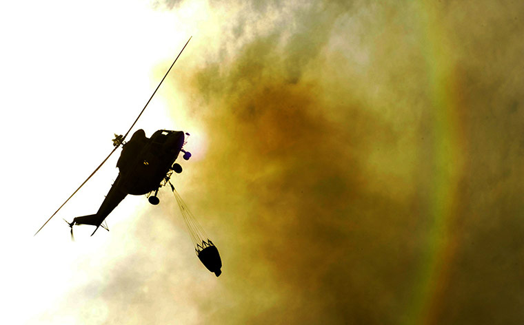 A helicopter flies over a fire