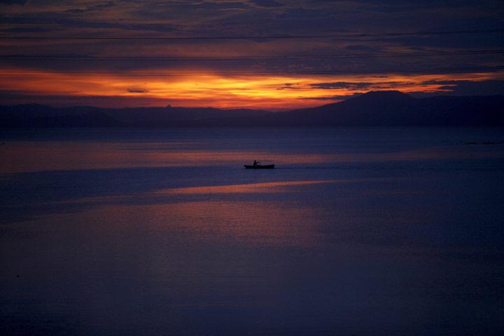 A boat crosses Tipitapa river at sunset in Managua, Nicaragua