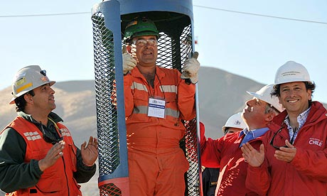 Workers inspect the rescue capsule to bring the trapped miners to the surface
