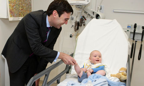Andy Burnham, meeting Ethan Crew at Manchester Children's hospital, says Labour will fight NHS plans