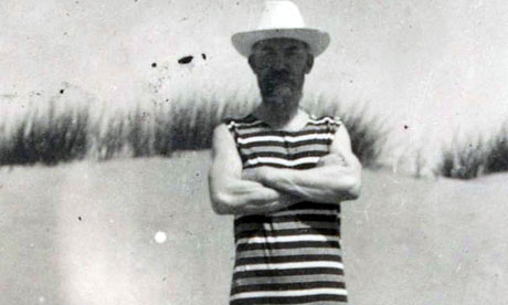 George Bernard Shaw standing on a beach in a  bathing suit and hat in 1903