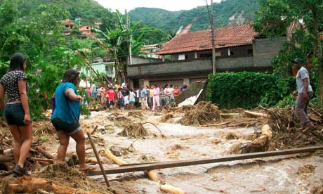 Women trying to cross a river after landslides in Brazil