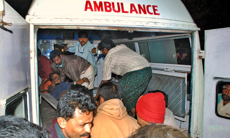 An injured Hindu pilgrim is carried into an ambulance after the accident in Kerala, India