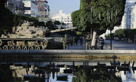 Soldiers stand guard near a tank on a street of Tunis on 16 January 2011.