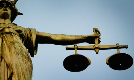 A statue holding the scales of justice on top of the Old Bailey