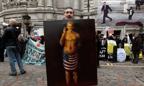 A demonstrator holds a painting of Tony Blair outside the Chilcot inquiry on 21 January 2011.