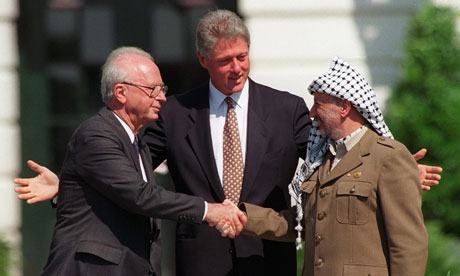 Bill Clinton watches Yitzhak Rabin and Yasser Arafat shake hands over the Oslo peace accords