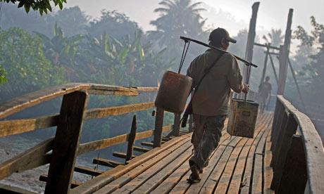 A Myanmar man carries water over a bridg