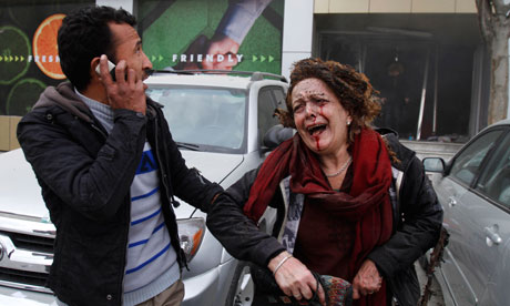 An injured woman is escorted out of the supermarket hit by a suicide bomber in Kabul, Afghanistan