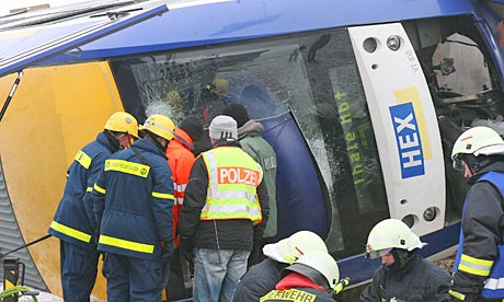 German rescuers check a derailed commuter train that collided with a cargo train