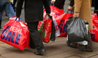 Shoppers carry bags from the post-Christmas sales on Oxford Street.