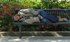 A homeless person sleeping on a public bench.