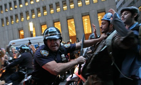 A police officer shoves a protester affiliated with the Occupy Wall Street protests