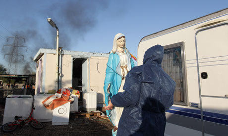 A resident moves a figure of the Virgin Mary from Dale Farm travellers camp
