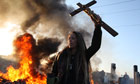 An activist holds up a crucifix as a barricade burns during evictions from Dale Farm