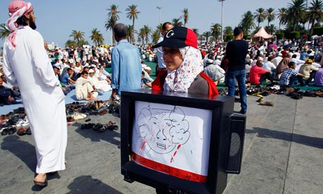 A girl carries a TV with a drawing of Muammar Gaddafi in Martyrs Square, Tripoli, Libya