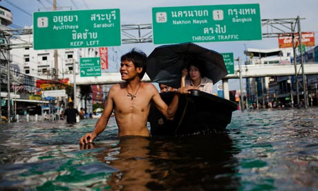 Thai residents make their way through a flooded street in Pathum Thani, Thailand.