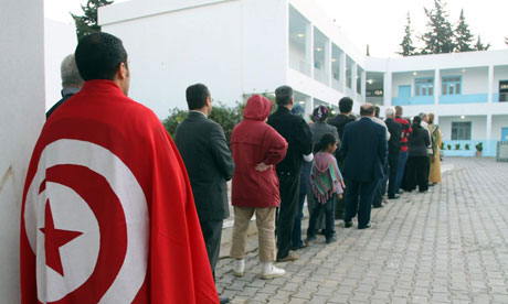 Voters, one draped in the national flag, queue up outside a polling station in Tunisia