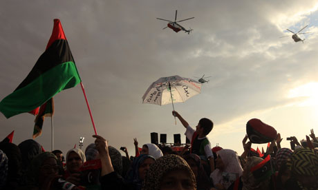 Libyan people look at helicopters flying above them during celebrations liberation of Libya Benghazi