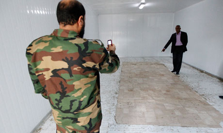 Anti-Gaddafi fighter takes photo inside storage freezer where body of Muammar Gaddafi was displayed