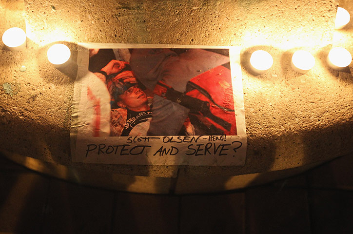 A picture of Scott Olsen is surrounded by candles  via guardian.co.uk