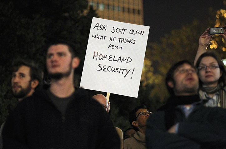 A protester holds up a sign referencing Scott Olsen via guardian.co.uk