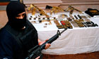 A masked  policeman stands guard next to weapons seized from the Zetas gang