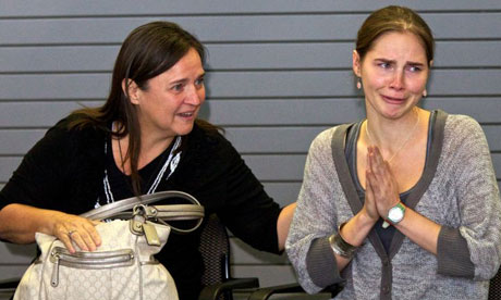 Amanda Knox acknowledges the cheers of supporters while her mother, Edda Mellas, comforts her