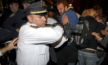 A senior New York police officer swings his baton at Occupy Wall Street protesters