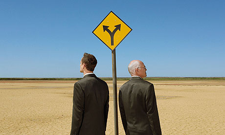 Two businessmen with briefcases standing by road sign in desert