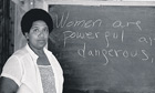Audre Lorde in front of a blackboard that says 'Women are powerful and dangerous'
