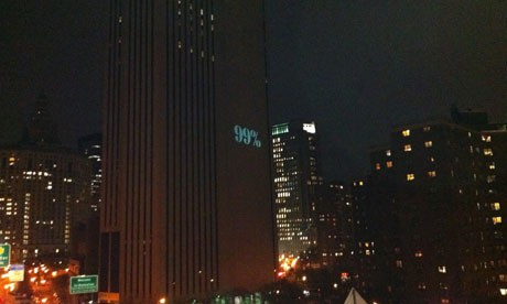 Occupy Wall Street slogan is projected onto the Verizon building in New York