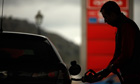 A worker pumps petrol into a customer's car at a petrol station