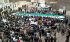 Anti-Assad demonstrators wave the former Syrian flag in Deraa province