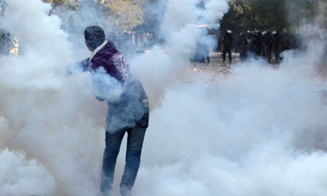 An Egyptian anti-government protester throws a teargas canister back at riot police in Tahrir Square