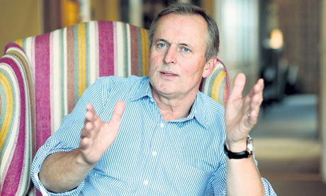 John Grisham sitting in a stripy armchair