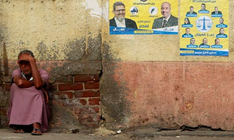 A beggar sits beside election posters for the Muslim Brotherhood's Freedom and Justice party