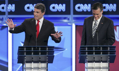 Mitt Romney listens to Texas governor Rick Perry during the CNN Republican debate in Washington, DC.