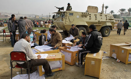 Egyptian officials count ballots at an open-air election centre in Cairo