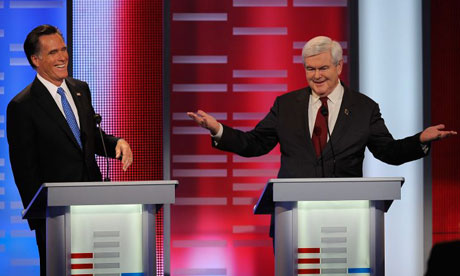Mitt Romney laughs as Newt Gingrich speaks at the Republican debate in Iowa.