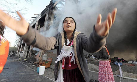 A woman gestures at Roma camp in Turin